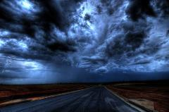 Image of storm, dark clouds with a road in a rural area